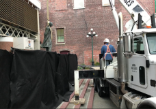 The statue being removed by a crane truck