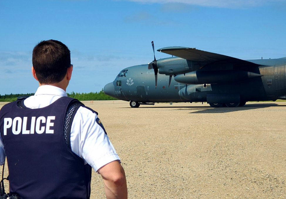 A RCMP member watches as a Royal Canadian Air Force aircraft arrives in Gillam, MB to assist in the manhunt (Photo: Manitoba RCMP)
