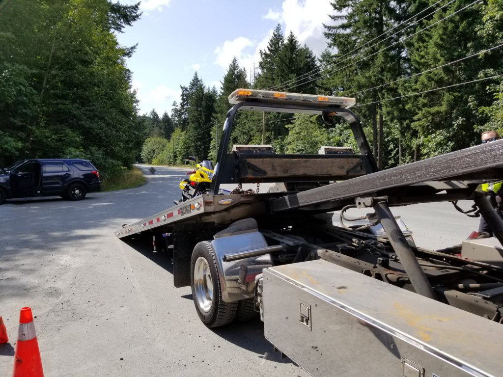 A motorcycle is towed on July 18, 2019, after the driver is stopped for allegedly speeding on Willis Point Road. (Saanich police)