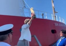 Vessel sponsor and marine scientist Dr. Verena Tunnicliffe of the University of Victoria breaks a champagne bottle against the hull of the Sir John Franklin (Canadian Coast Guard)