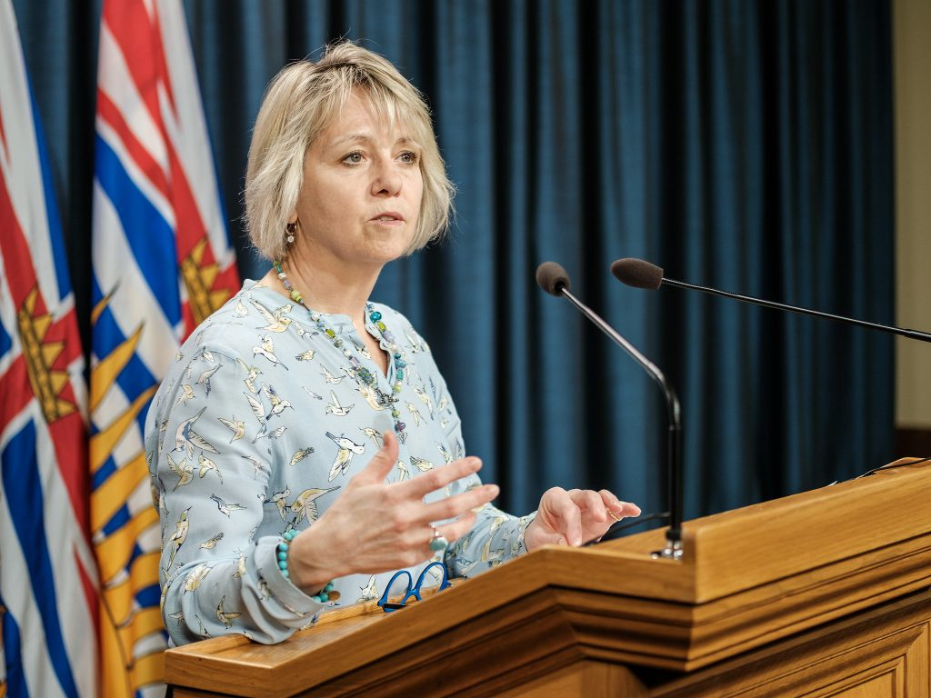 Dr. Bonnie Henry at the podium, giving B.C.'s COVID-19 update, wearing a blue blouse with yellow hummingbirds on it
