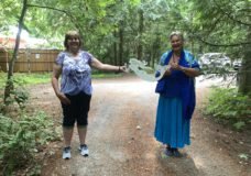 Amy Sanderson handing over the mermaid sign she found, returning it to Renate Herberger,