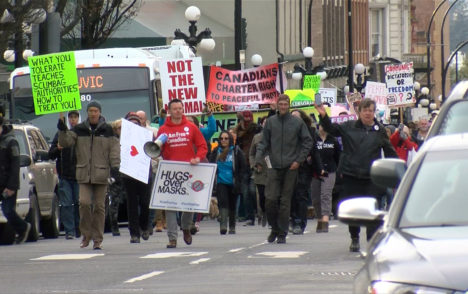 Anti-mask protesters march through downtown Victoria, hold rally